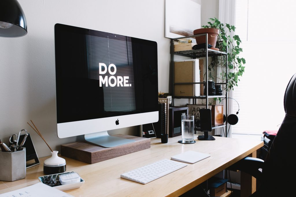 Modern desk with Do More on imac screen